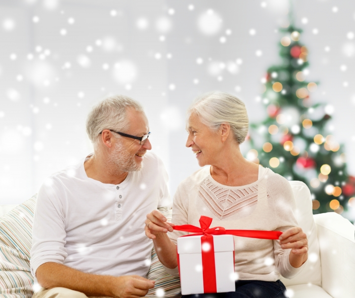 happy-senior-couple-with-gift-box-at-home